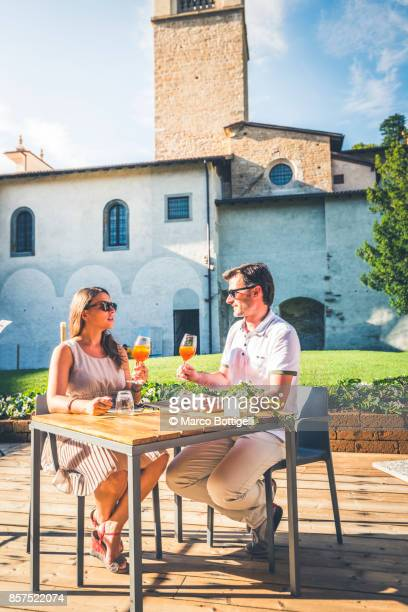 Couple drinking cocktail in a cloister, Italy