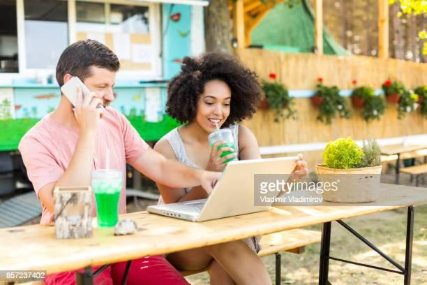 Couple de boire des cocktails et de l'utilisation de portable dans la nature