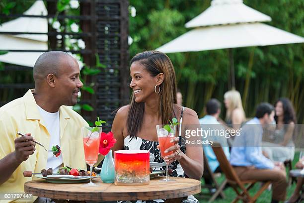 Couple drinking cocktails at restaurant patio