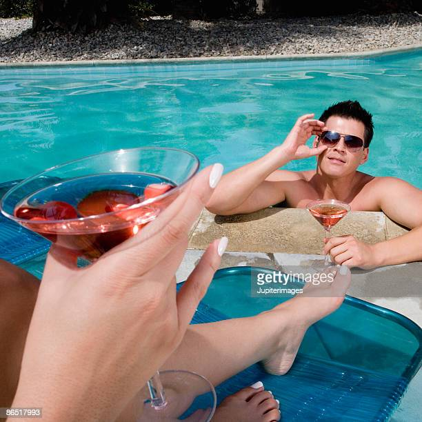 Couple drinking cocktails poolside