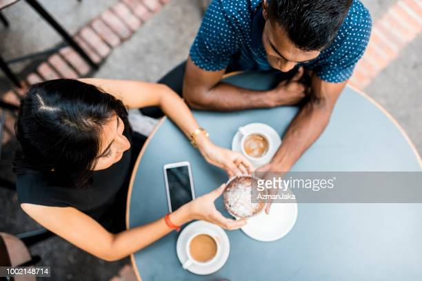 couple drinking coffee and eating dessert at a cafe - muslim couple stock pictures, royalty-free photos & images