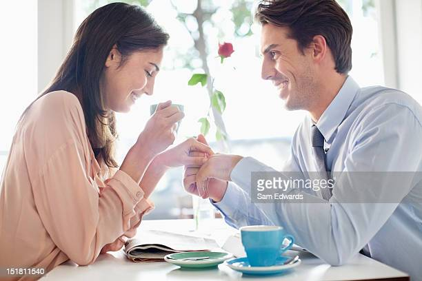 Couple drinking coffee and holding hands in cafe