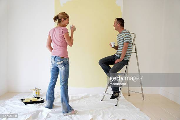 Couple Drinking Coffee and Looking at Freshly Painted Wall