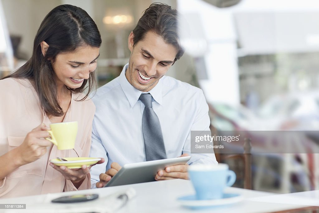Couple drinking coffee and using digital tablet in cafe window : Stock Photo