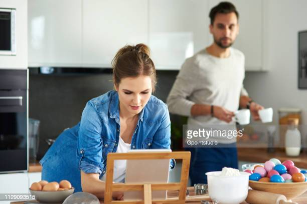 Couple drinking coffee and using digital tablet in kitchen