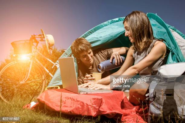 Couple drinking coffee and using laptop in camping tent