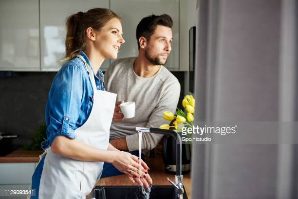 Couple drinking coffee and washing up in kitchen