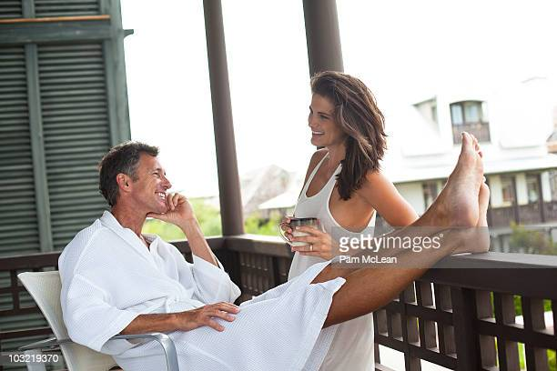 Couple drinking coffee on a cottage balcony