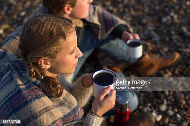Couple drinking coffee on beach