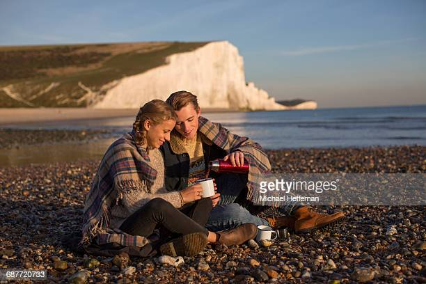 Couple drinking coffee on beach
