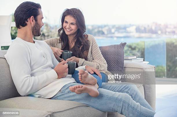 Couple drinking coffee on he sofa.