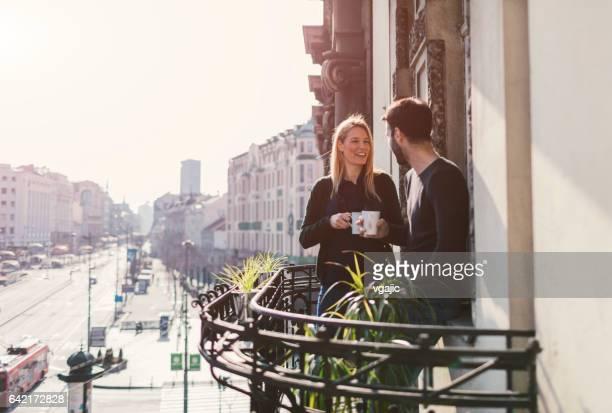Couple drinking coffee on hotel balcony