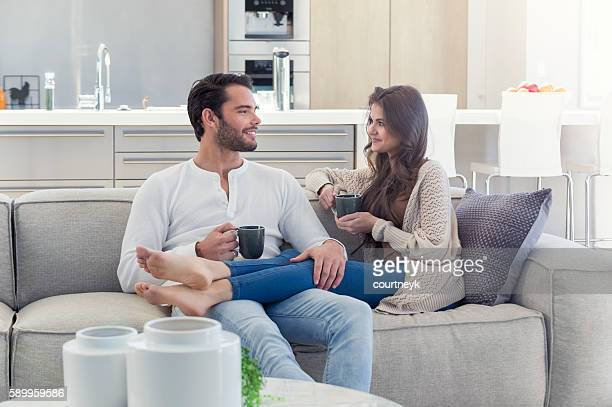 Couple drinking coffee on the sofa.