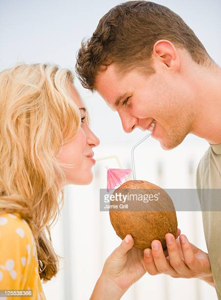 Couple drinking from coconut together