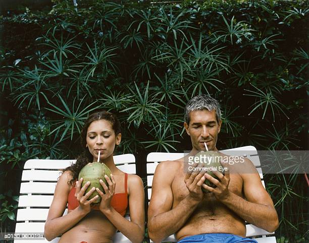 Couple Drinking From Coconuts