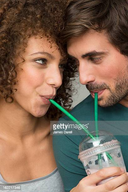 couple drinking from same cuo with straws