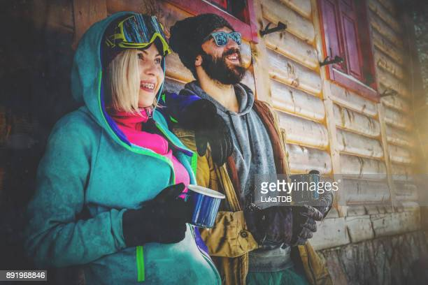 Couple drinking hot tea in front of cottage