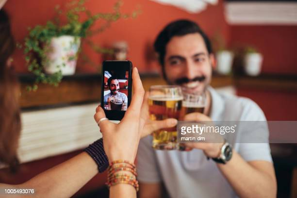 couple drinking in bar - photo messaging stock photos and pictures