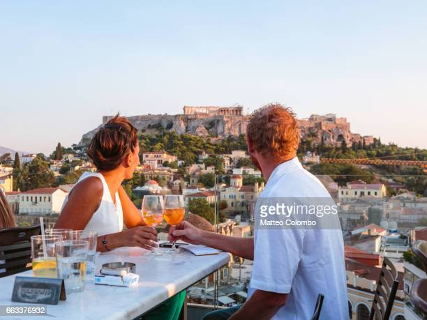 Couple drinking in front of the Acropolis at sunset. Athens, Greece