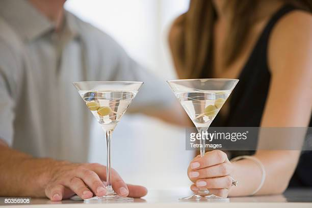 couple drinking martinis - mid section stock photos and pictures