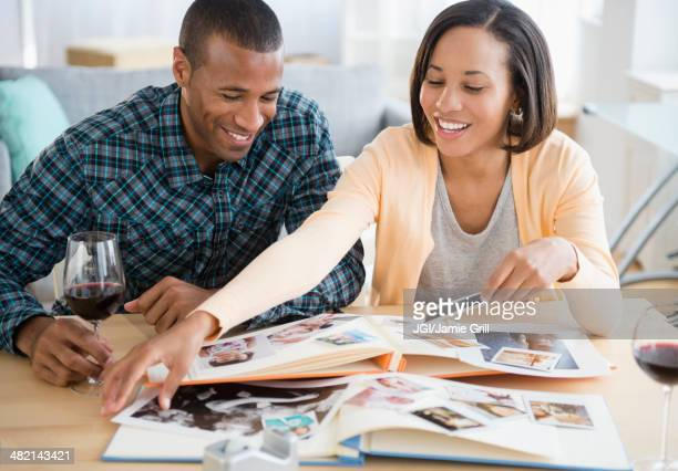Couple drinking red wine and looking at photographs