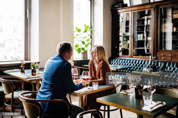 couple drinking red wine at restaurant table together - daten stockfoto's en -beelden