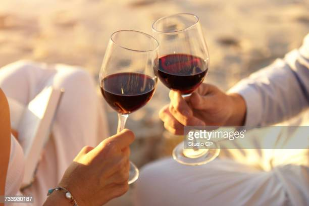Couple drinking red wine on beach