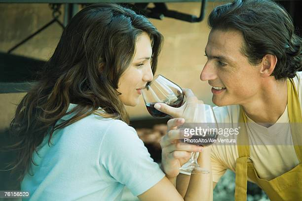 Couple drinking red wine with arms linked