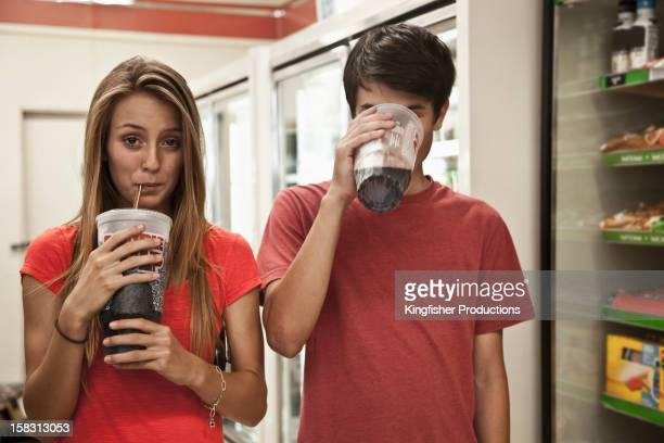 couple drinking soda - convenience store stock photos and pictures