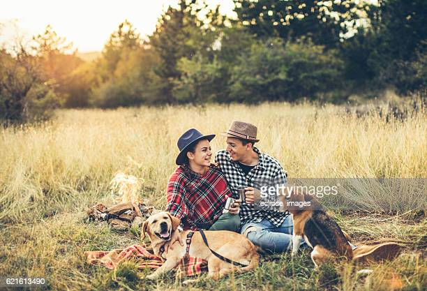 Couple drinking tea in front of bonfire