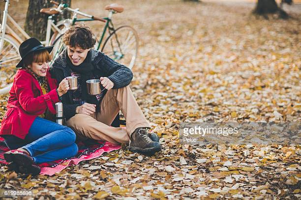 Couple drinking tea in park after a bicycle ride