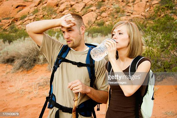 カップル飲料水でのハイキング