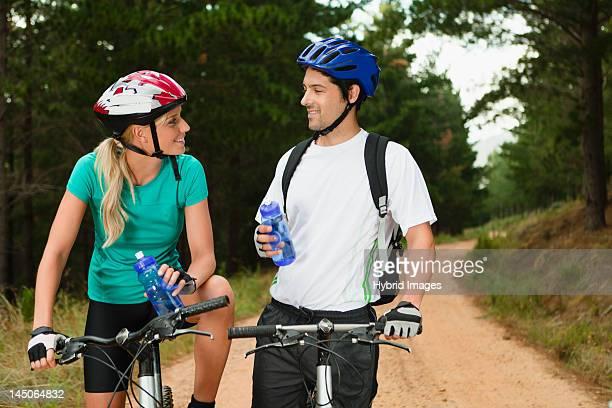 Couple drinking water on mountain bikes