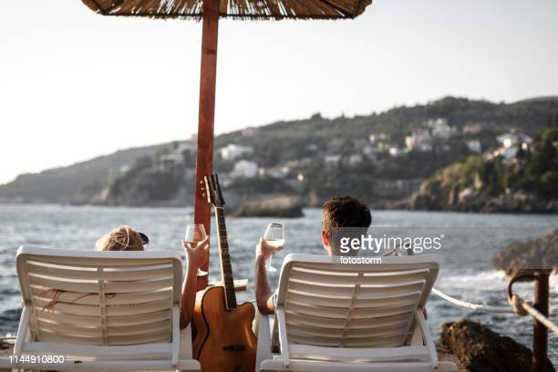Couple drinking wine and enjoying the view from the beach