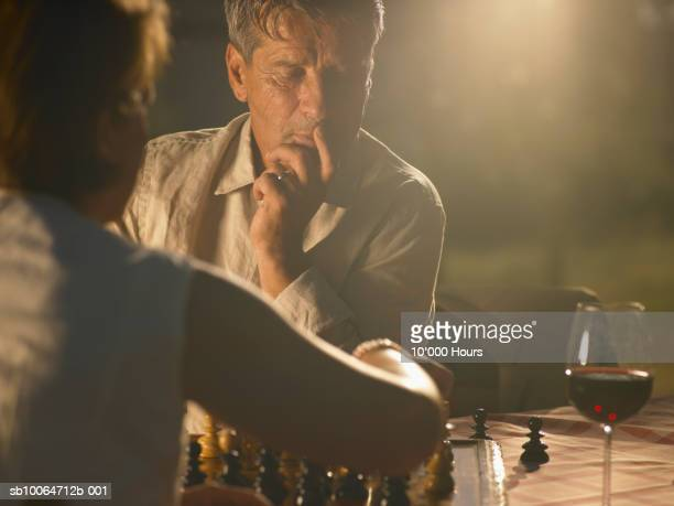 Couple drinking wine and playing chess outdoors