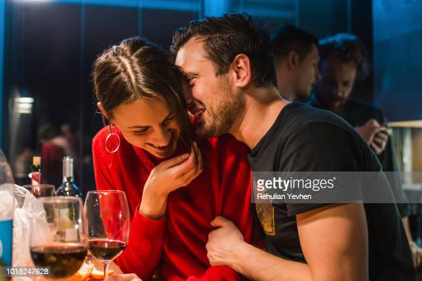 couple drinking wine at party in apartment - flirtare foto e immagini stock