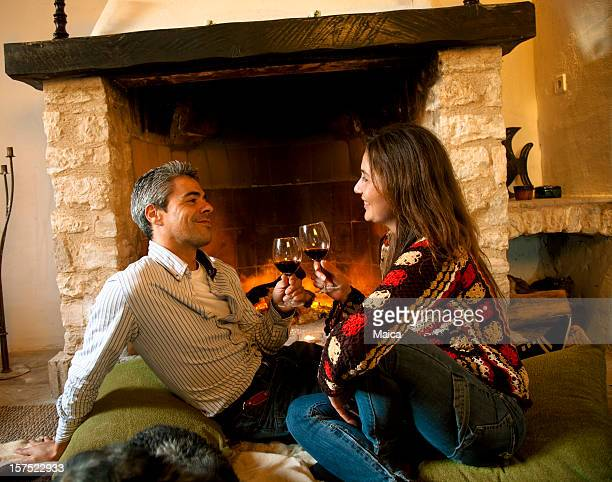 Couple, boire du vin près du feu