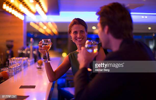 couple drinking wine in a hotel bar - flirting stock pictures, royalty-free photos & images