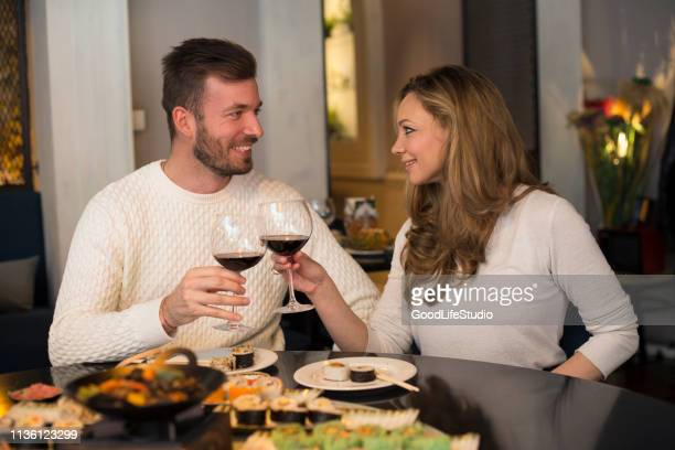 couple drinking wine in a restaurant - cabernet sauvignon grape stock pictures, royalty-free photos & images