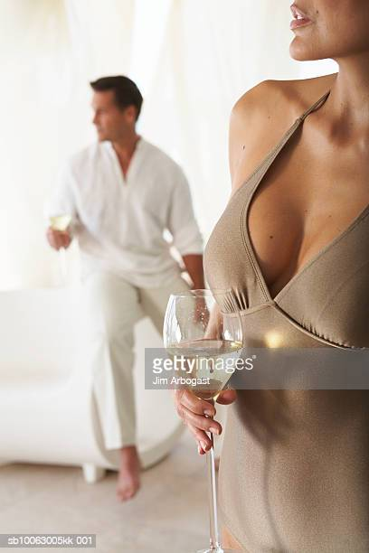 Couple drinking wine in room, focus on woman (mid section) in foreground