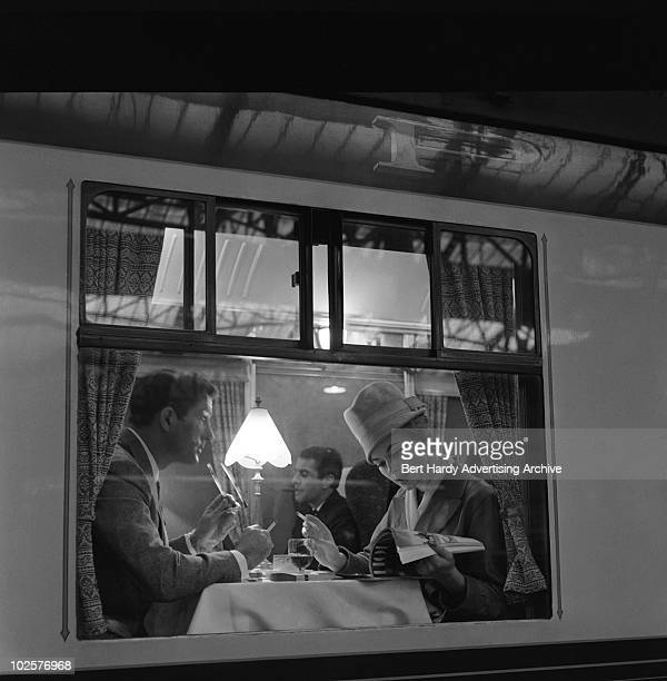A couple drinking wine in the dining car of the Golden Arrow train at Dover Kent 17th November 1960