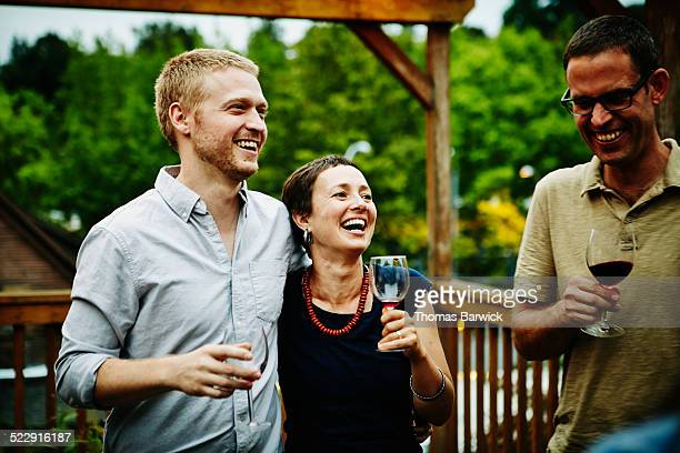 Couple drinking wine with friends on deck