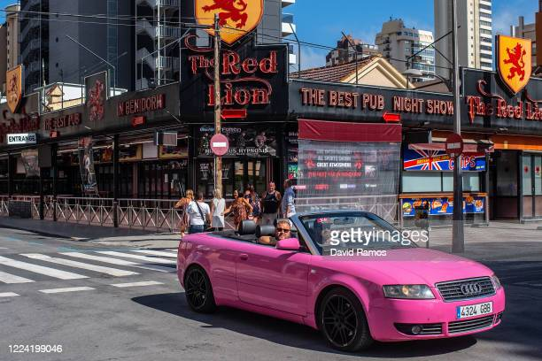 A couple drive their pink car past a closed Englishpub on May 11 2020 in Benidorm Spain Some parts of Spain have entered the socalled Phase One...