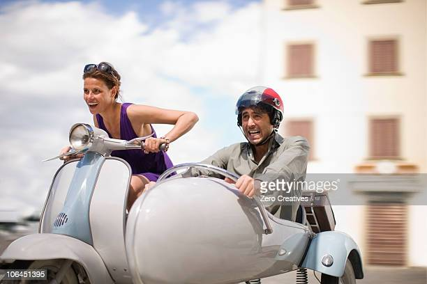 Couple driving a vespa