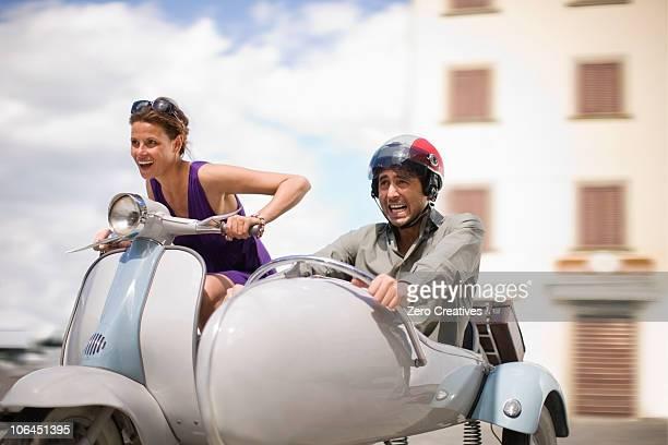 Couple driving a vespa