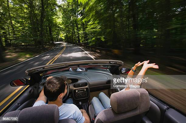 Couple driving along forest road