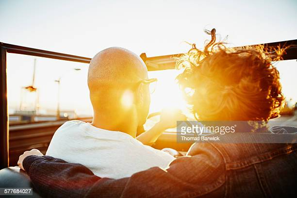 Couple driving convertible at sunset