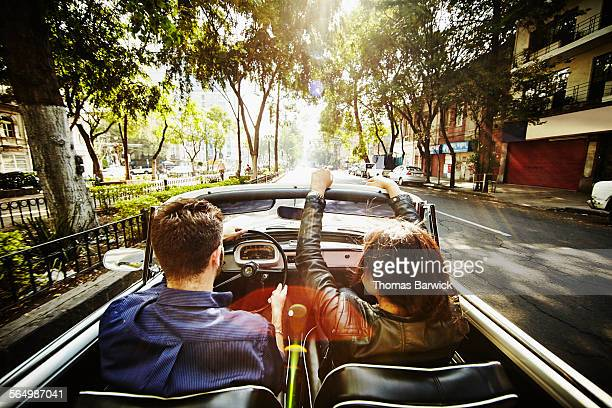 Couple driving convertible on city boulevard