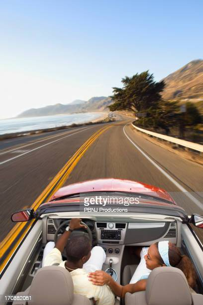Couple driving convertible on coastal road