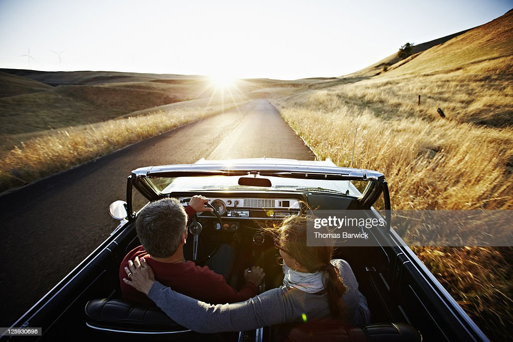 Couple driving convertible on empty road at sunset : Stock Photo